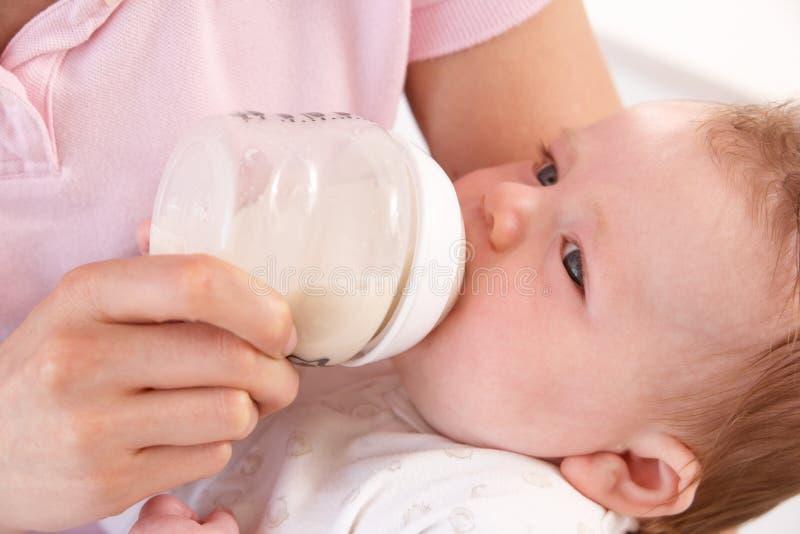 Moeder die Fles thuis geeft aan de Jongen van de Baby royalty-vrije stock afbeeldingen