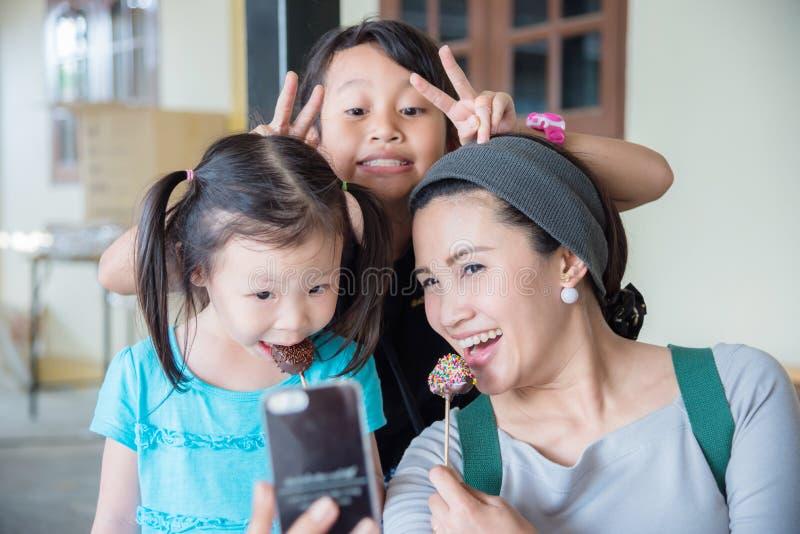 Moeder die foto met haar kind nemen door slimme telefoon stock fotografie