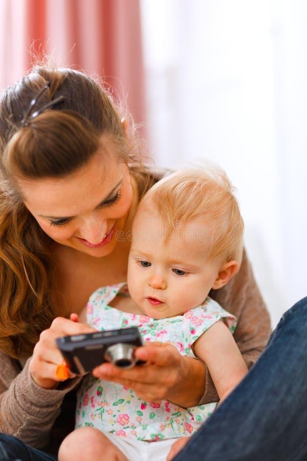 Moeder die geinteresseerde babyfoto's in camera toont royalty-vrije stock afbeeldingen
