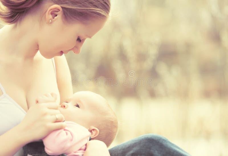 Moeder die haar baby in aard in openlucht in het park voeden royalty-vrije stock afbeeldingen