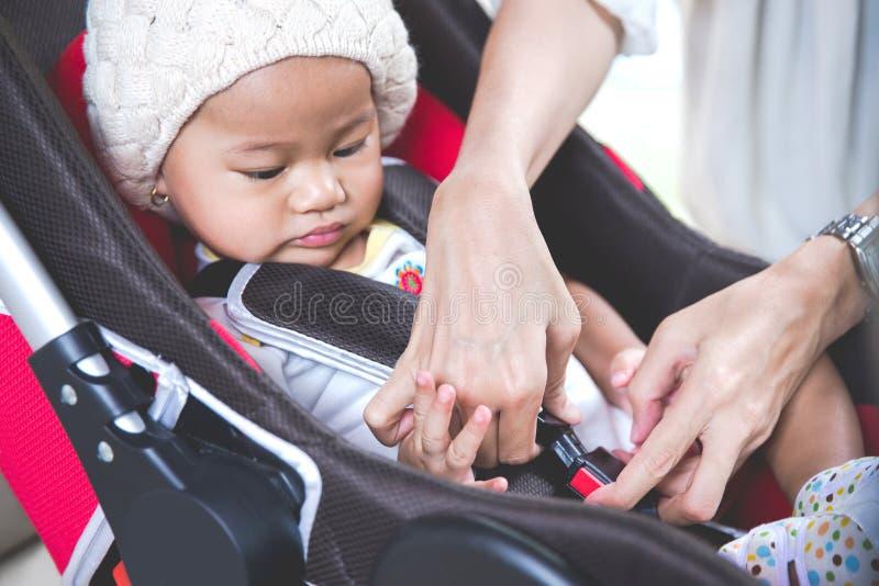 Moeder die haar baby in de autozetel beveiligen in haar auto stock foto
