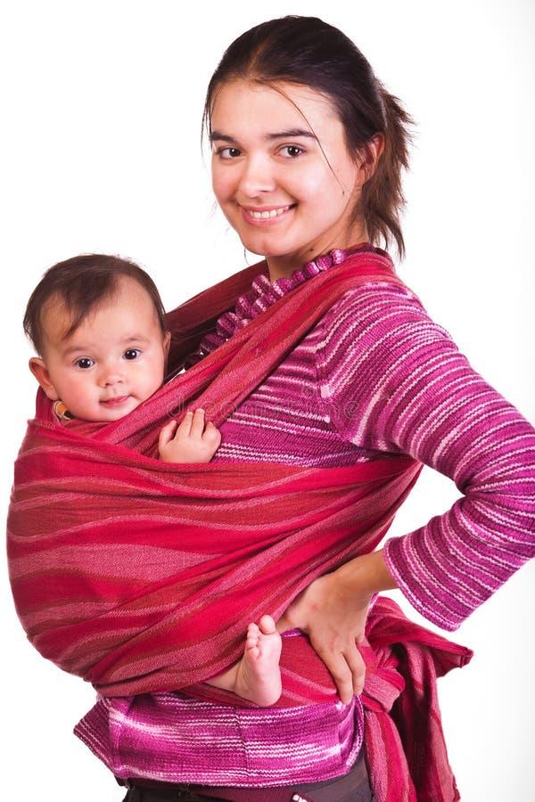 Moeder die haar baby in een slinger vervoert royalty-vrije stock foto