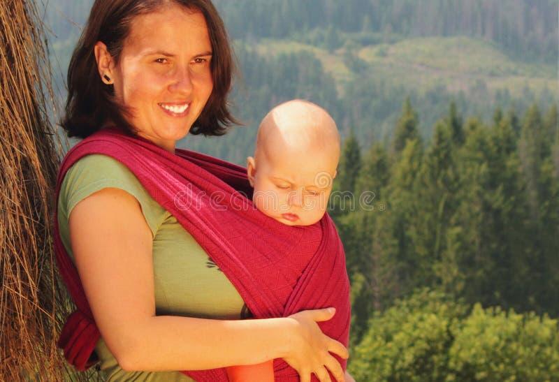 Moeder die haar baby in een slinger vervoert stock fotografie