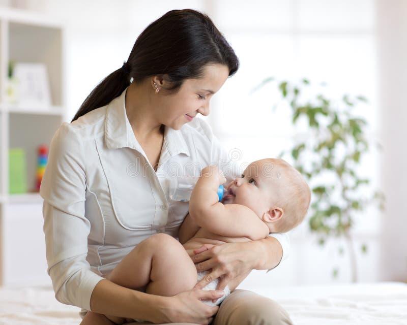 Moeder die haar baby op de slaapkamer voeden stock afbeelding
