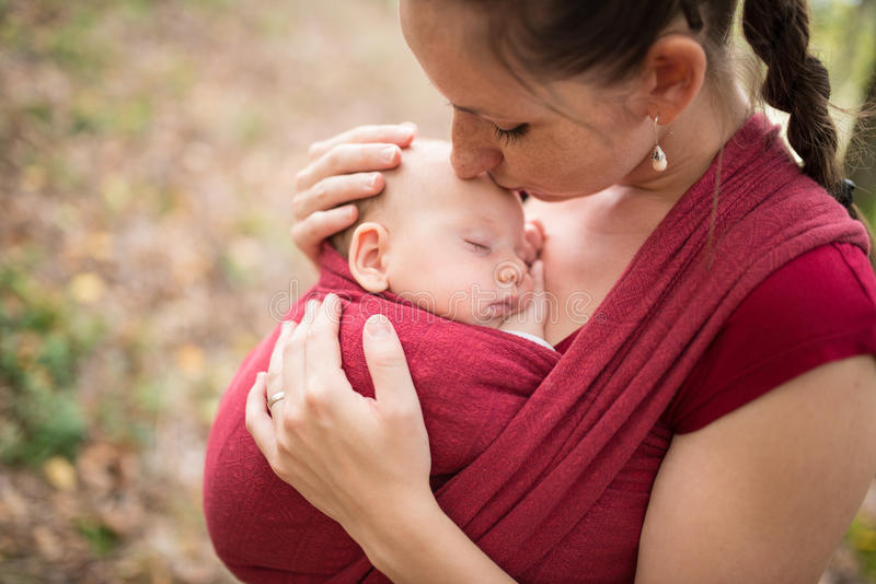Moeder die haar babydochter, buitenkant in de herfstaard houden stock afbeelding