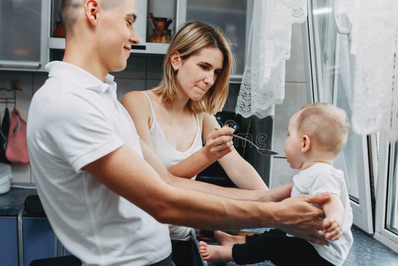 Moeder die haar babydochter met lepel voeden royalty-vrije stock afbeeldingen
