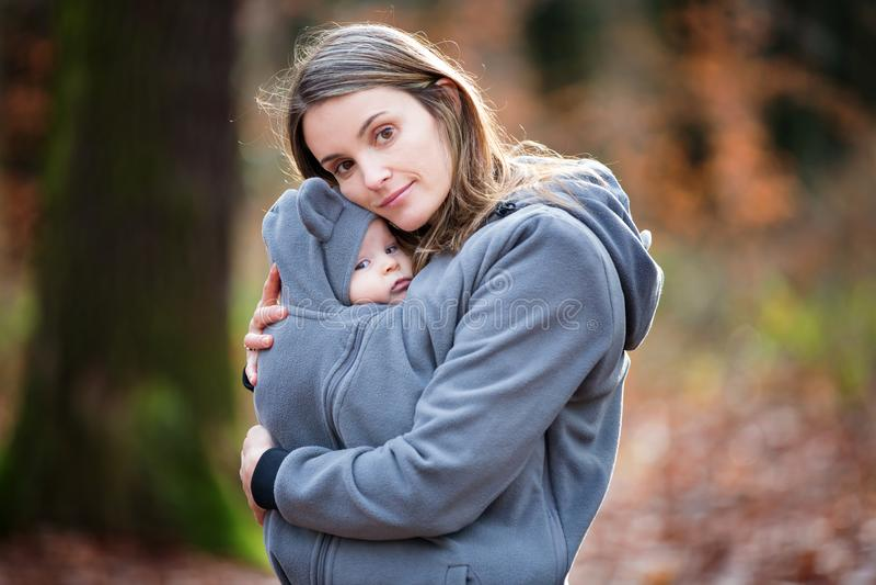 Moeder, die haar babyjongen in een slinger vervoeren, in openlucht stock fotografie