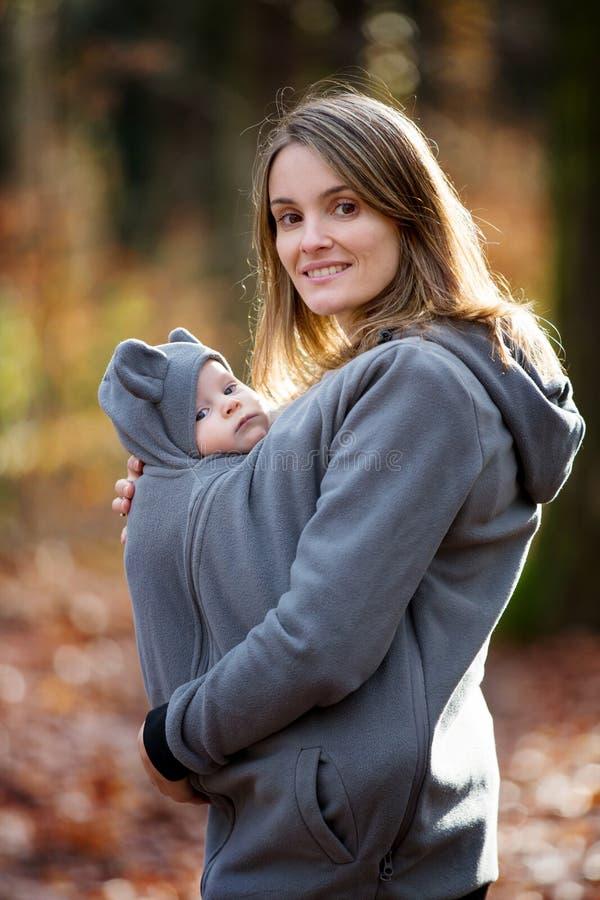Moeder, die haar babyjongen in een slinger vervoeren, in openlucht royalty-vrije stock afbeeldingen