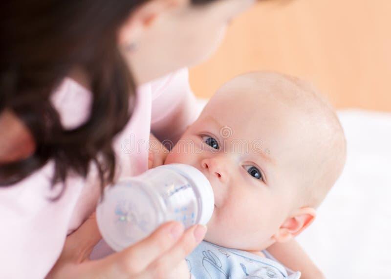 Moeder die haar babyjongen met fles voeden stock foto