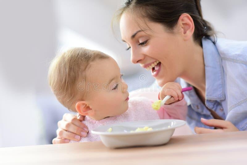 Moeder die haar babymeisje het eten bevorderen stock afbeeldingen