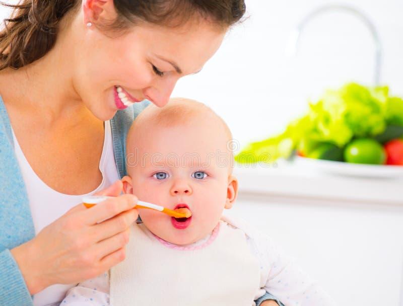 Moeder die haar Babymeisje met een lepel voeden stock afbeeldingen