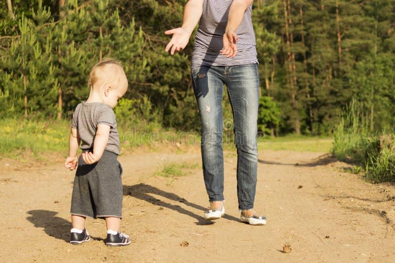 Moeder die haar de jongenszoon van de één jaarbaby voor het lopen onderwijzen Schuwe peuter die eerste stappen proberen te maken royalty-vrije stock afbeelding