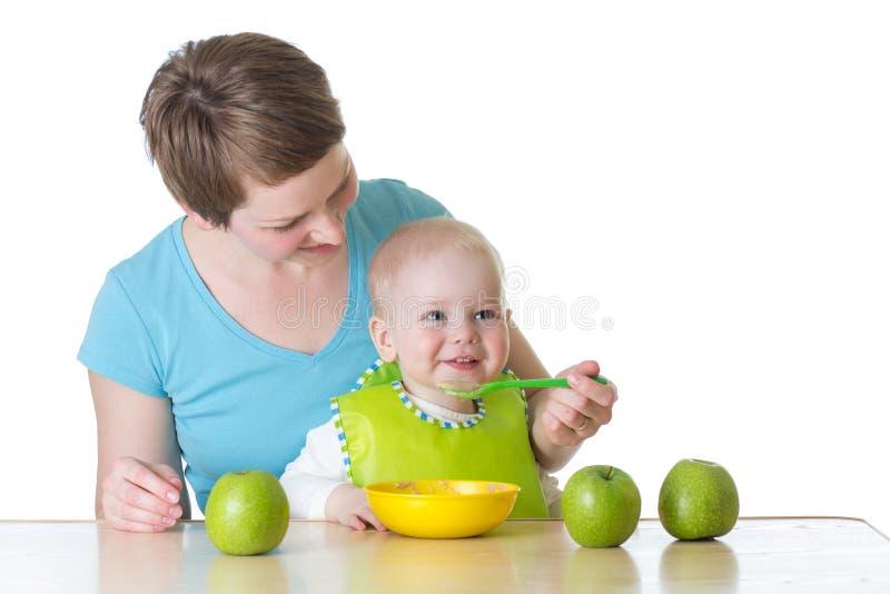 Moeder die haar die baby met de lepel voeren op wit wordt geïsoleerd stock fotografie