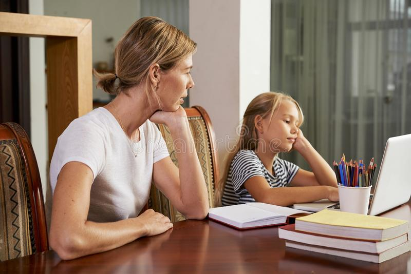 Moeder die haar dochter bekijken die thuiswerk doen stock foto