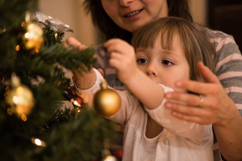 Moeder die haar dochter helpen Kerstmisboom verfraaien royalty-vrije stock afbeeldingen
