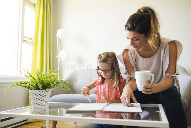 Moeder die haar dochter helpen tijdens haar thuiswerk in de woonkamer stock afbeelding
