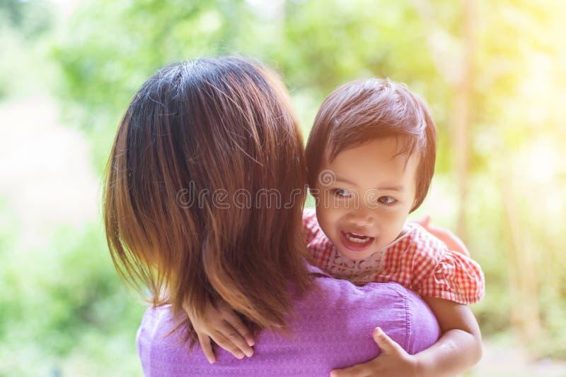 Moeder die haar dochter houdt stock afbeeldingen