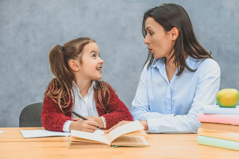 Moeder die haar dochter met het schoolthuiswerk helpt stock afbeeldingen