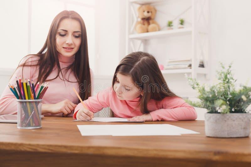 Moeder die haar dochter met het thuiswerk helpt stock foto