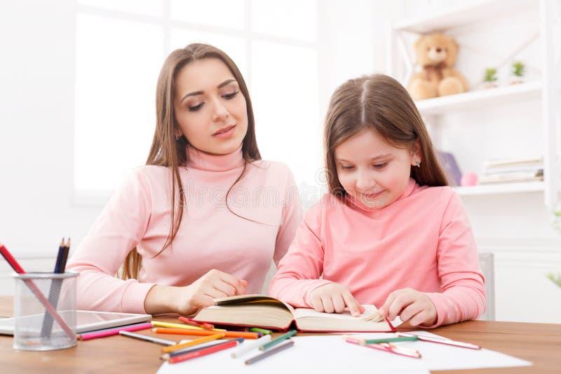 Moeder die haar dochter met het thuiswerk helpt royalty-vrije stock afbeeldingen