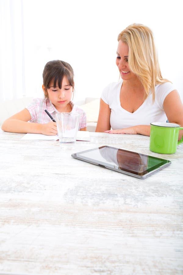 Moeder die haar dochter met het thuiswerk helpt stock afbeelding