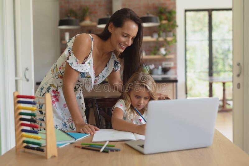 Moeder die haar dochter met thuiswerk in een comfortabel huis helpen royalty-vrije stock fotografie