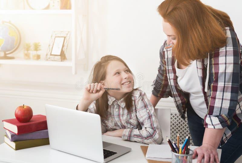 Moeder die haar dochter met thuiswerk helpt stock afbeelding
