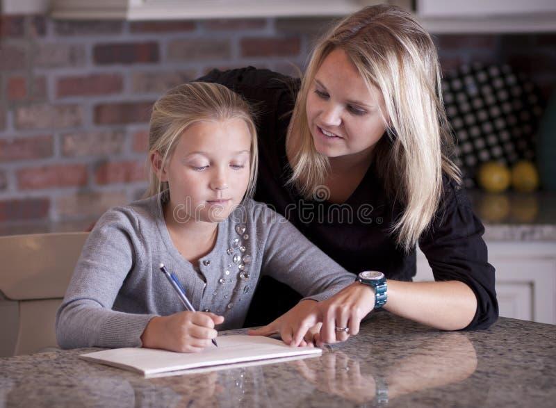 Moeder die haar dochter met thuiswerk helpt royalty-vrije stock foto