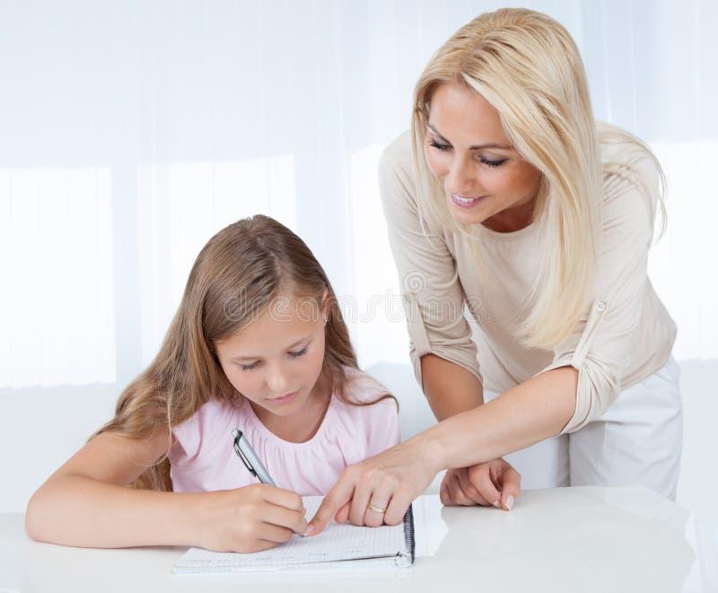 Moeder die Haar Dochter met Thuiswerk helpt stock foto