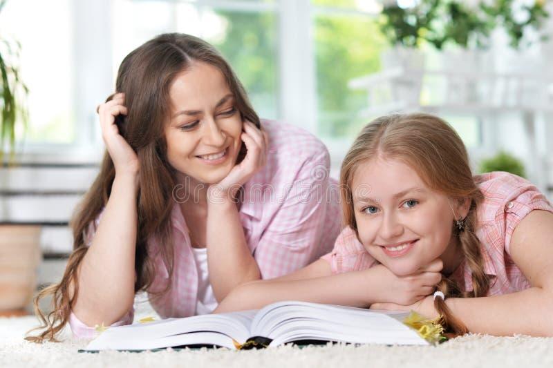 Moeder die haar dochter met thuiswerk helpt stock afbeeldingen