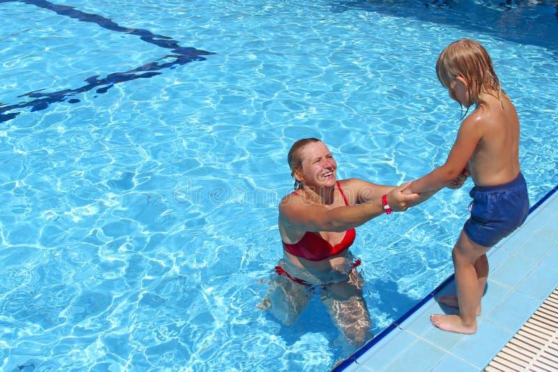 Moeder die haar dochter vangen springend in zwembad Gelukkige Vakantie royalty-vrije stock fotografie