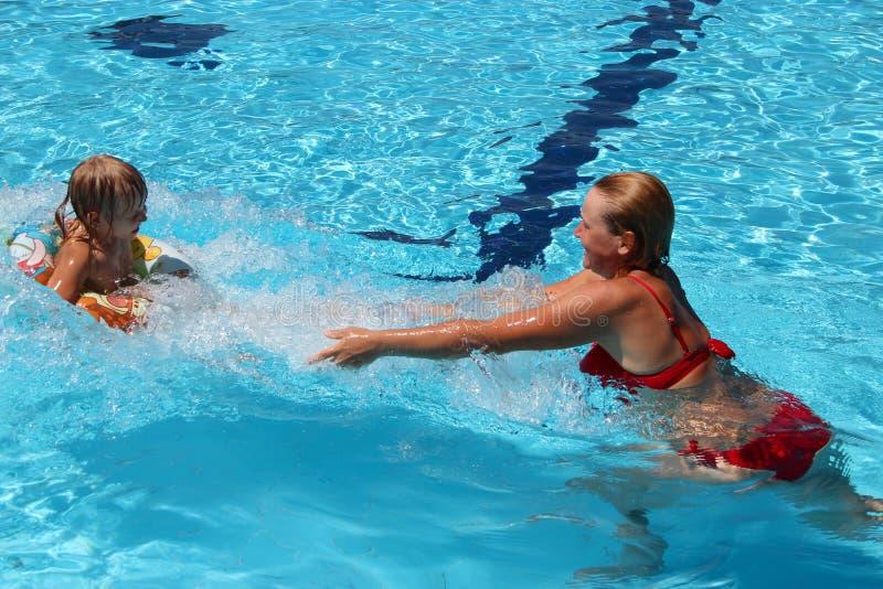 Moeder die haar dochter vangen springend in zwembad Gelukkige Vakantie stock foto