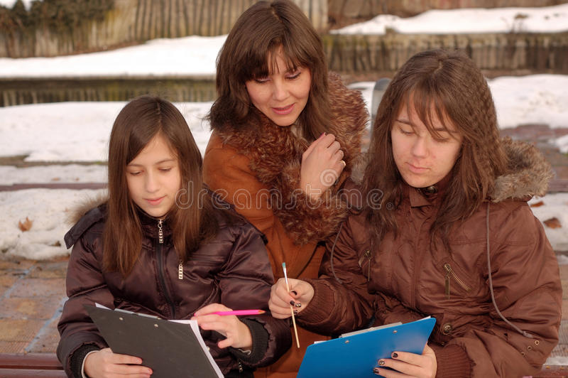 Moeder die haar dochters onderwijst stock afbeeldingen