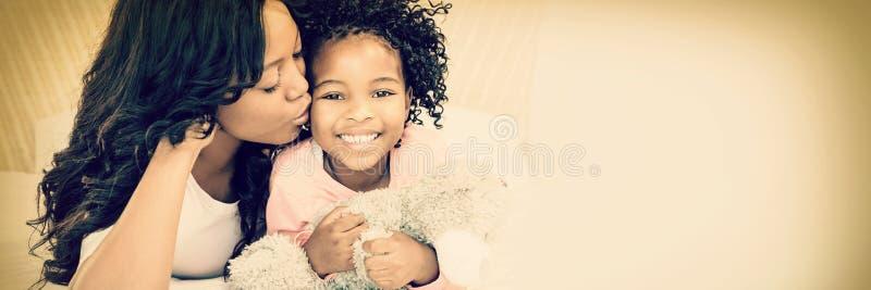 Moeder die haar glimlachende dochter op bed kussen royalty-vrije stock fotografie