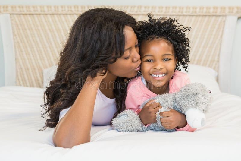 Moeder die haar glimlachende dochter op bed kussen stock fotografie