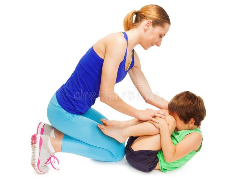 Moeder die haar jong geitjezoon onderwijzen die gymnastiek maken stock fotografie