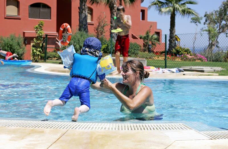 Moeder die haar jonge zoon helpt om in een zonnige swimmin te zwemmen en te springen stock fotografie