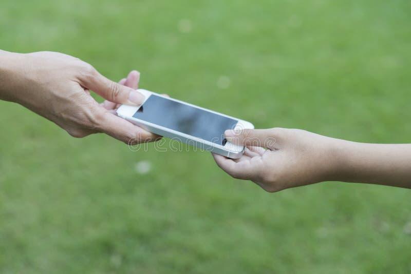 Moeder die haar kind een mobiele telefoon geven royalty-vrije stock fotografie