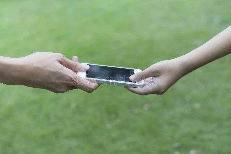 Moeder die haar kind een mobiele telefoon geven royalty-vrije stock afbeelding