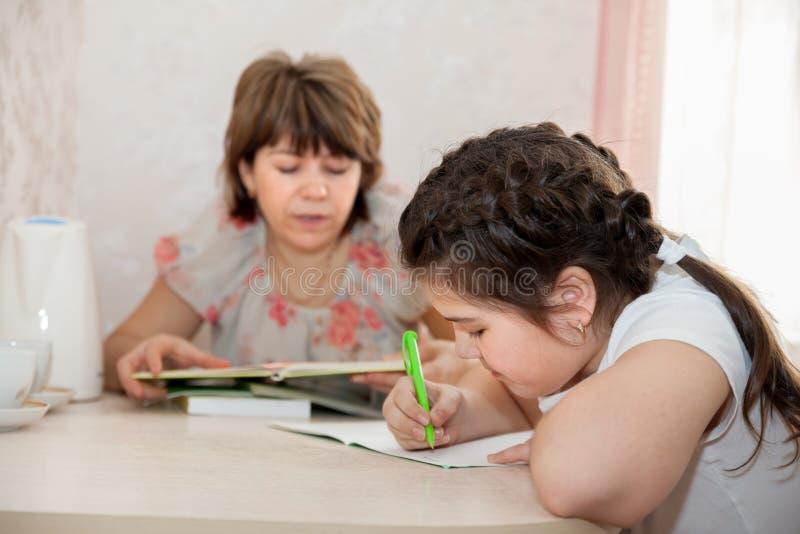 Moeder die haar kind met thuiswerk helpt stock afbeeldingen