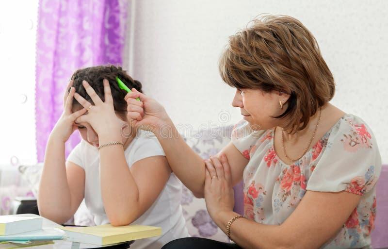 Moeder die haar kind met thuiswerk helpt stock afbeelding