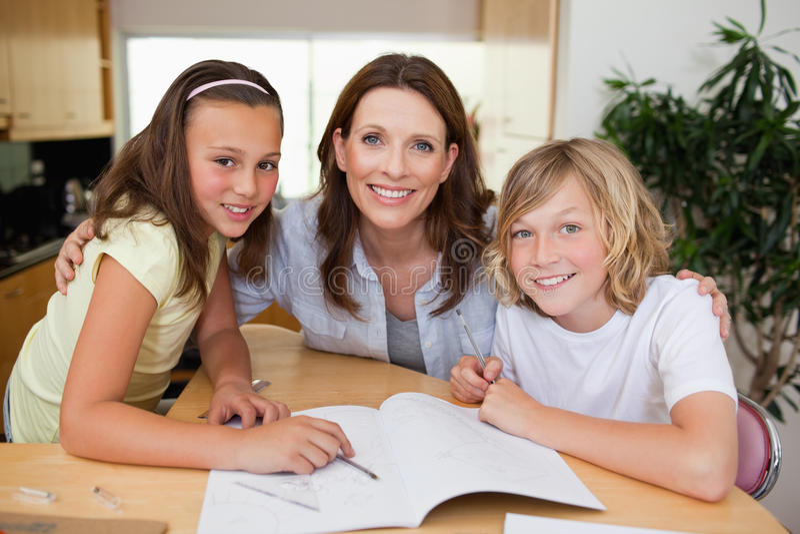 Moeder die haar kinderen met thuiswerk helpen royalty-vrije stock foto