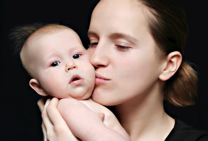 Moeder die haar kust weinig baby stock foto's