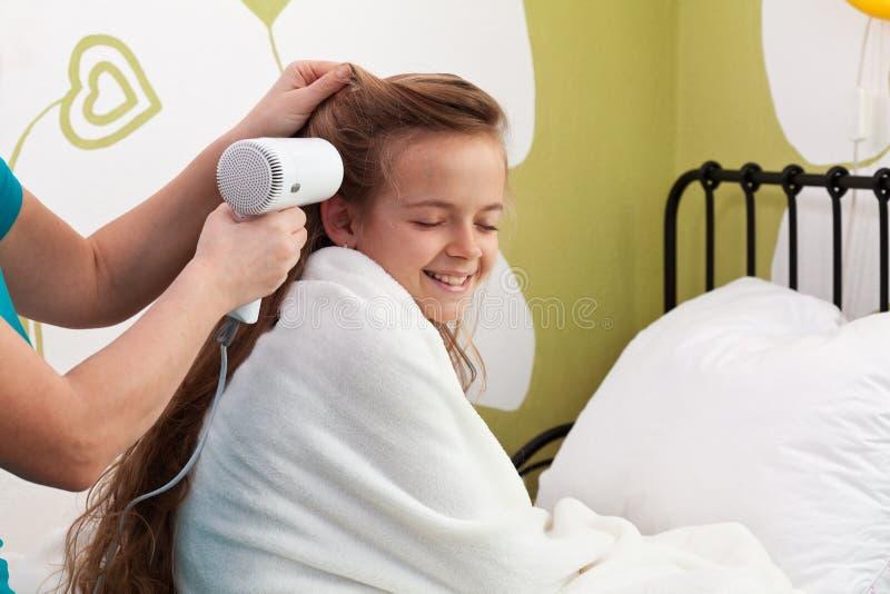 Moeder die haar meisje` s haar na bad drogen stock fotografie