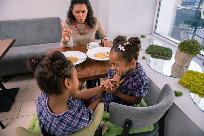 Moeder die haar meisjes voor slecht gedrag in restaurant berispen stock fotografie