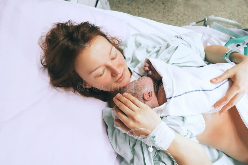 Moeder die haar pasgeboren baby na arbeid in het ziekenhuis houdt royalty-vrije stock afbeeldingen