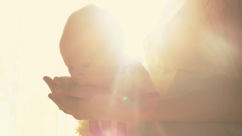 Moeder die haar pasgeboren babymeisje in handen houden tegen opvlammende zon royalty-vrije stock fotografie