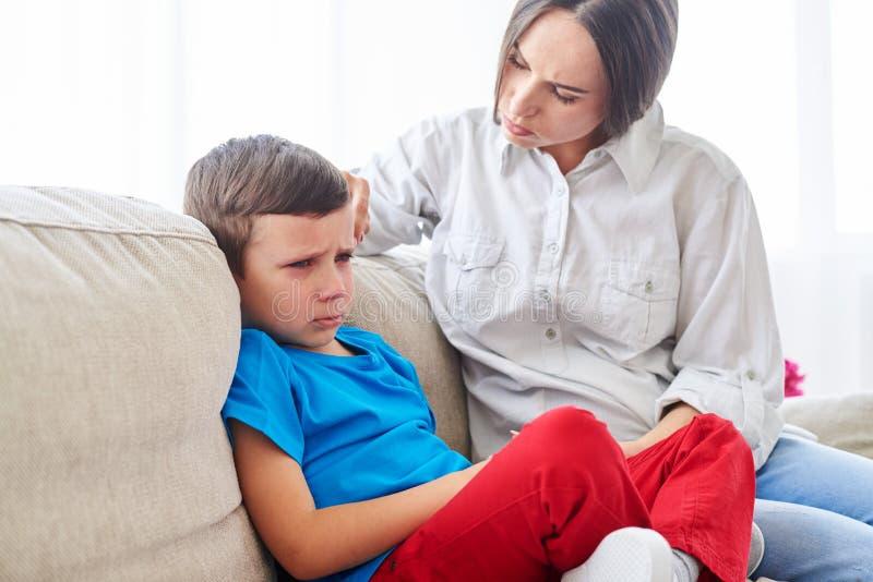 Moeder die haar teleurgestelde zoon proberen te troosten en te kalmeren royalty-vrije stock foto