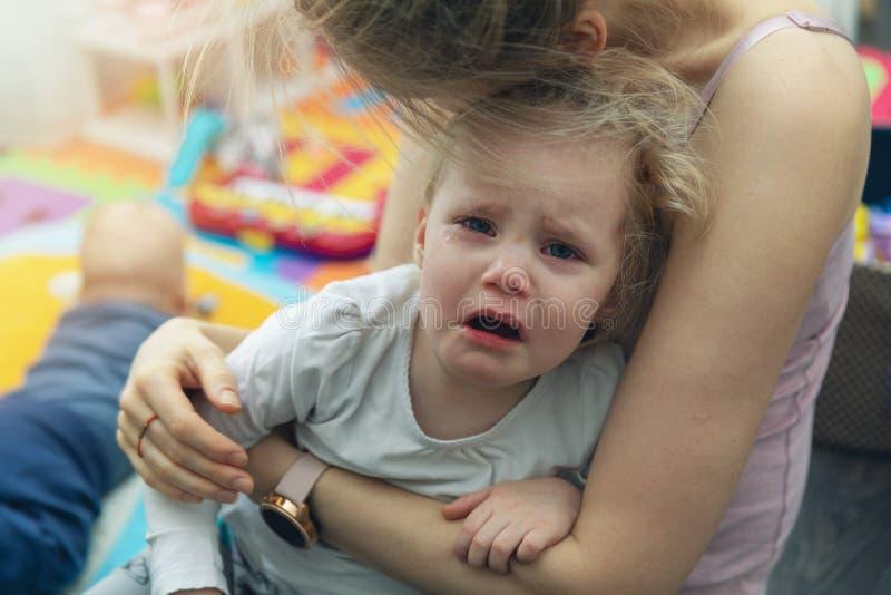 Moeder die haar troosten die weinig kind schreeuwen royalty-vrije stock fotografie