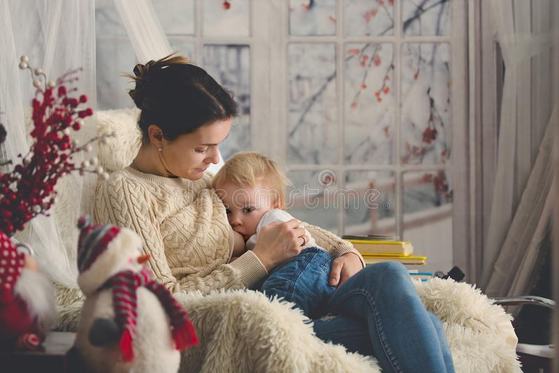 Moeder die haar zitting van de peuterzoon in comfortabele leunstoel de borst geven, wintertijd stock foto's